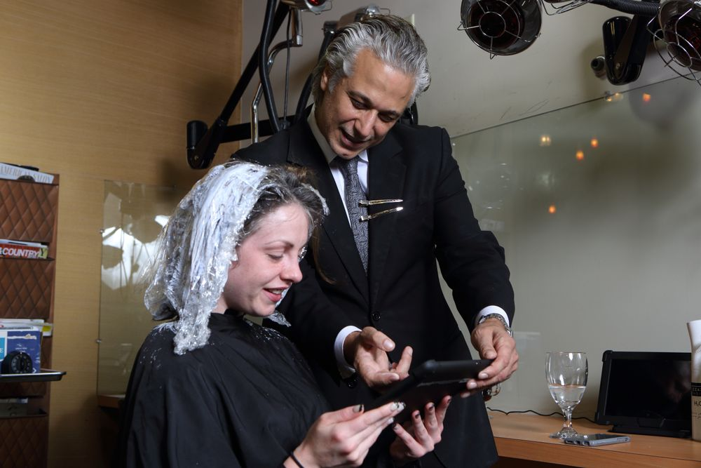 Cornacchione hands a tablet to a client while she is processing. Since using the system, the salonalso  learned that clients welcomes a chairside checkout option during high traffic times.
