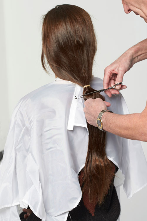 1. Begin with the cut. Remove the length. Direct the hair back to the nape. Place in a ponytail and cut below the elastic.