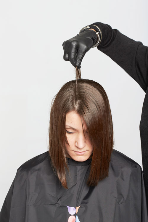1. For color, comb the hair as it is to be worn. Isolate a 1/8-inch section along the parting.