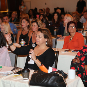 A HAIR+ Summit attendee poses a question during a salon-professional panel.