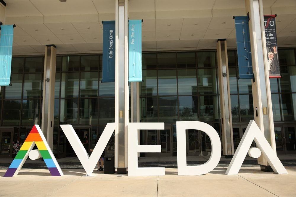 <p>A rainbow Aveda logo welcomes attendees.</p>