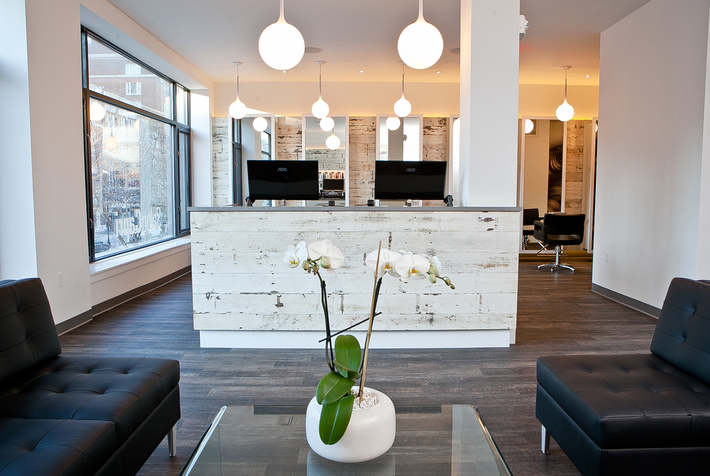 The space includes a spacious reception area with large, sun-lit glass windows to welcome guests to the salon.