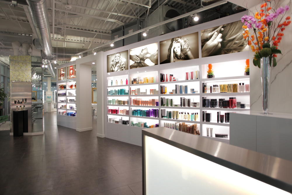 The lighting of the retail shelves that flank the reception desk beckon shoppers.