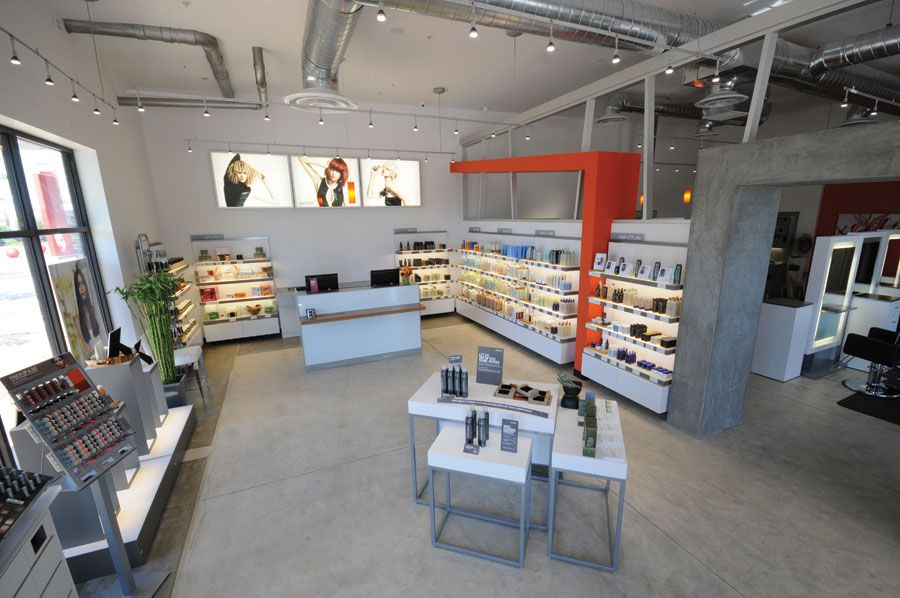 "Todd worked with Eurisko's Dr. Leon Alexander to create this sophisticated retail space with dramatically lit, modern shelving and oversized photography in light boxes. ""The orange/red accent color adds warmth to the coolness of the white shelves, concrete floors and aluminum accents,"" says Todd."