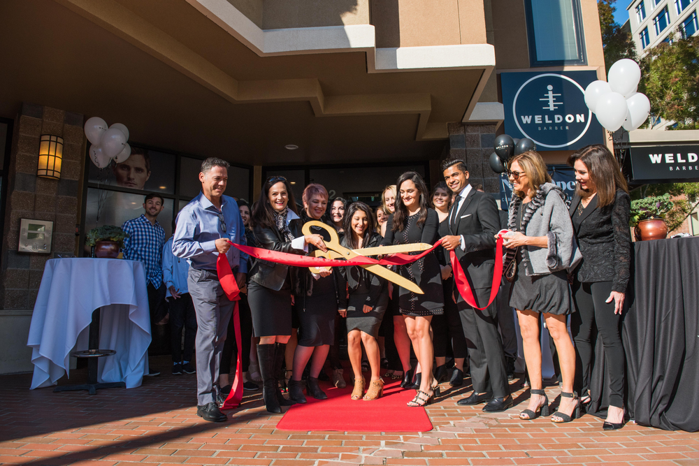 Teams from Weldon Barber and J.Hilburn celebrate their new partnership with a ribbon cutting for the new location.
