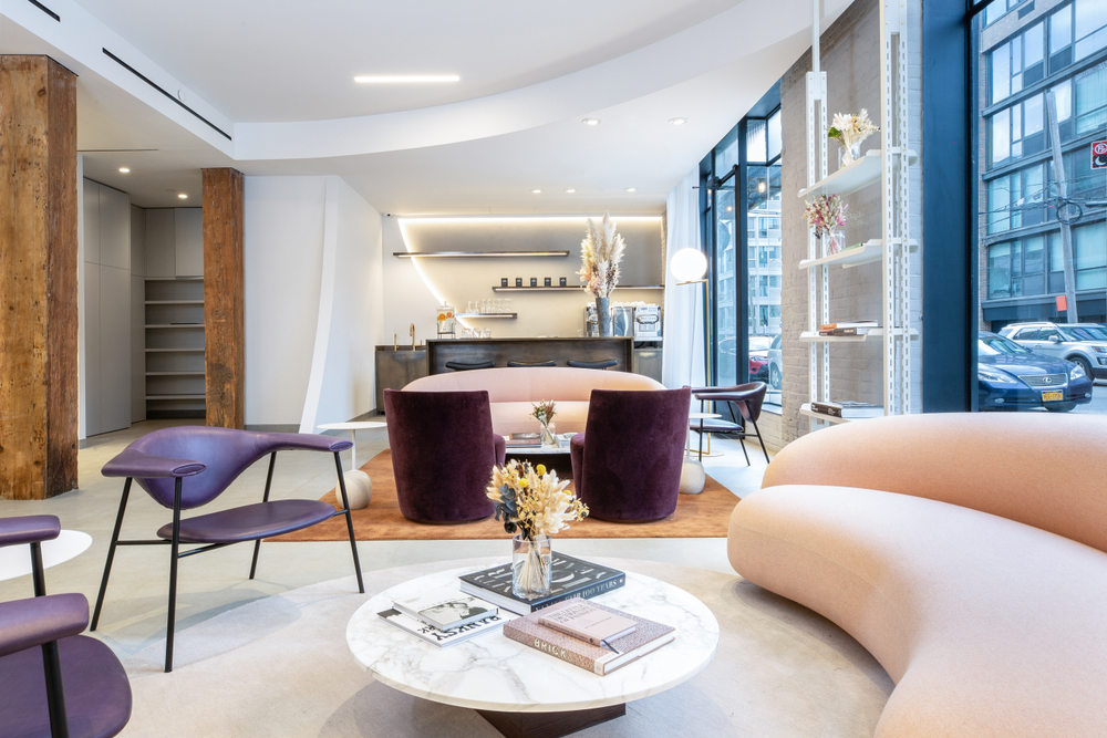 A dusty pink Italian sofa and bold purple velvet chairs combined with the bar creates a reception area that doubles as event space at Rob Peetoom Williamsburg in Brooklyn, New York.