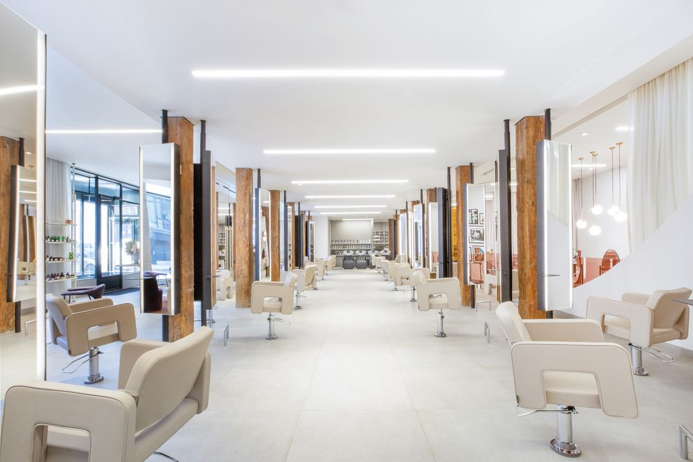 <p>At Rob Peetoom Williamsburg, the salon floor is punctuated by crisp white chairs, light stone tiles and century-old dark wood columns.</p>