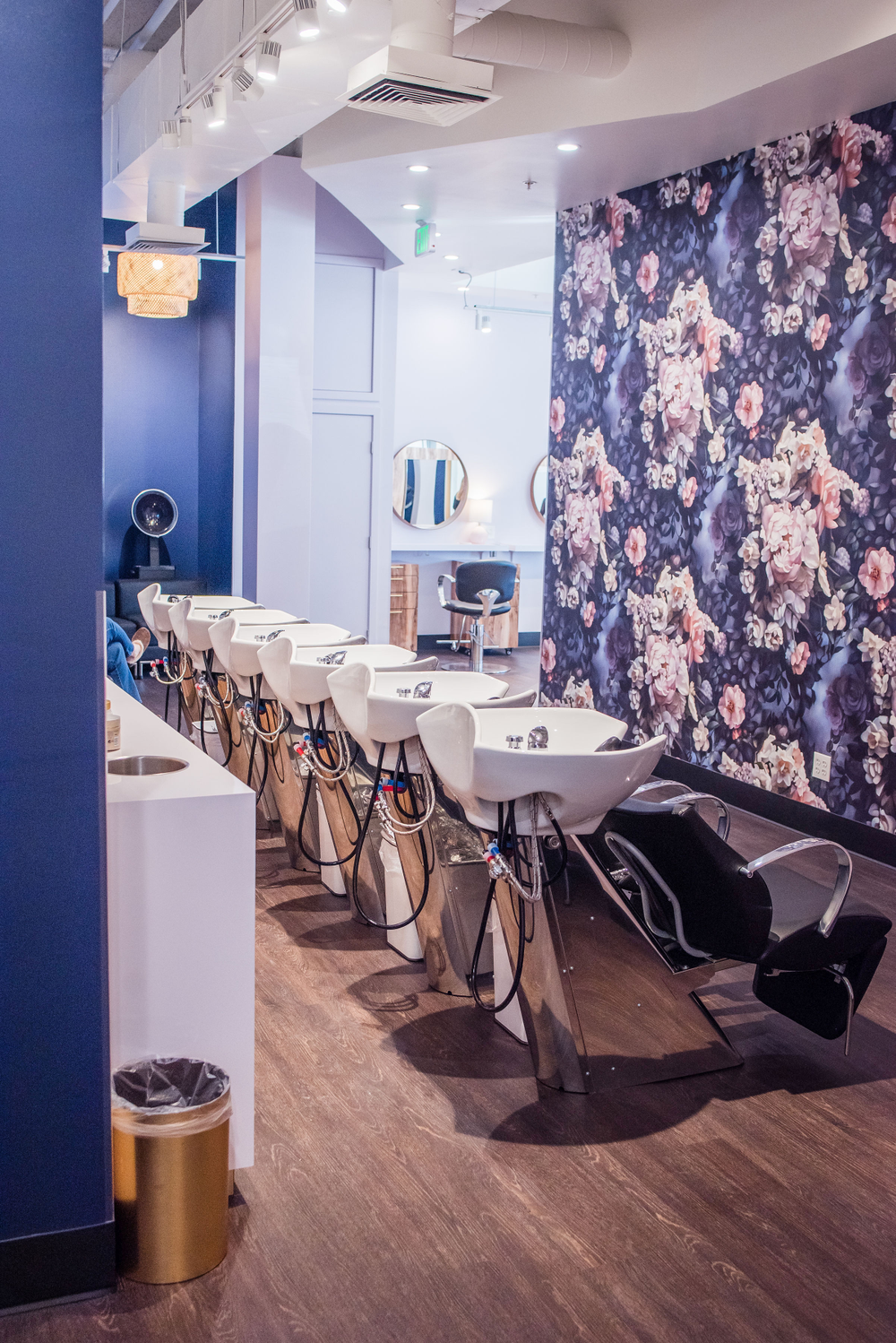 Colorful floral wallpaper and deep blue walls bring a smile to the faces of guests in the shampoo room at Salon Cosabella in Broomfield, Colorado.
