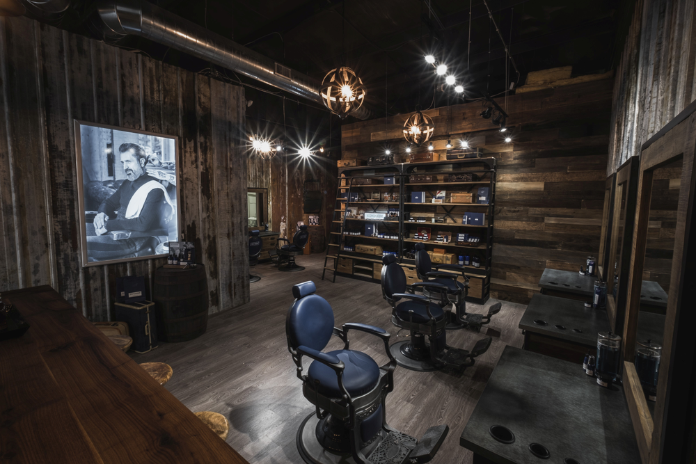 Alternating walls of shiplap and aged metal barn siding creates a rugged, masculine feel within 1922 Men's Grooming.
