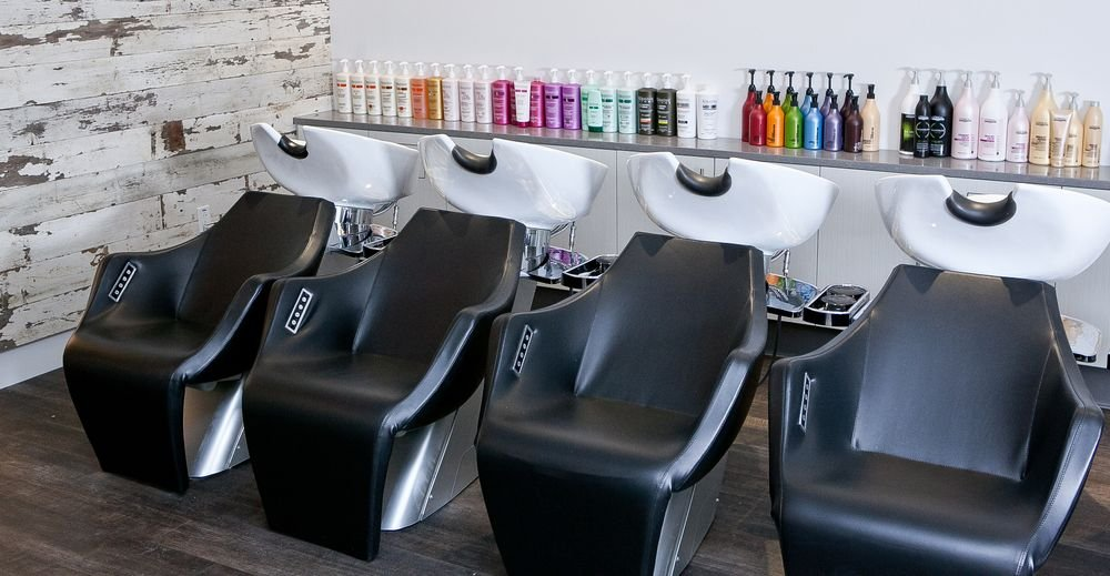 The shampoo & rinse area features reclining black leather massage chairs.