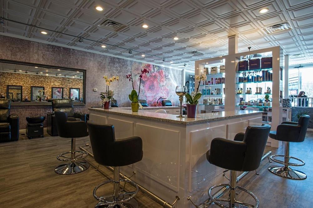 The salon's focal point is a custom designed multipurpose service bar that divides the hair styling and nail care areas while still maintaining an open feel that promotes conversation and interaction by everyone at the salon. The bar was built with large hidden cabinets keep all the styling tools out of sight until needed, allowing stylists to perform blow outs, hair color services or even manicures.