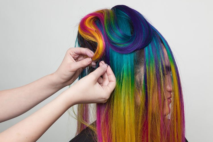 """5. """"Waterfall"""" the hairpiece down and over. Take one section and create a snaking, curving S-shaped line of looping hair from the front of the head to the back."""