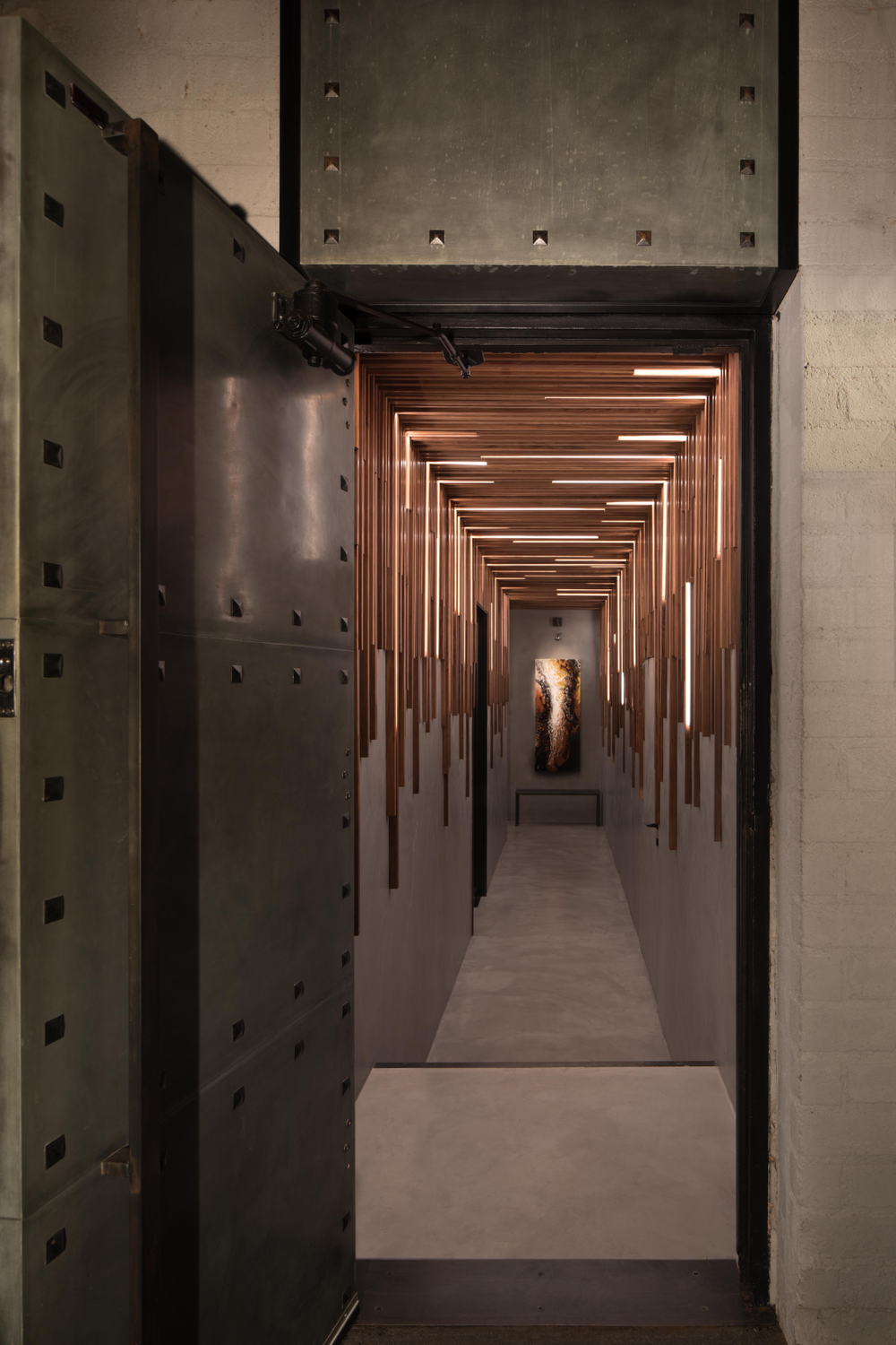 Like a modern-day speakeasy, guests access Totalee on the Alley in Beverly Hills, California, by pressing a doorbell at the steel door off the alley. Strategically placed wood pieces in the long seductively lit hallway creates a play of movement.