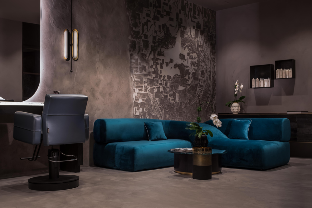 At Totalee on the Alley in Beverly Hills, a deep blue velvet X-shaped sofa under the salon's massive Brigitte Bardot mural provides cozy comfort for waiting guests.