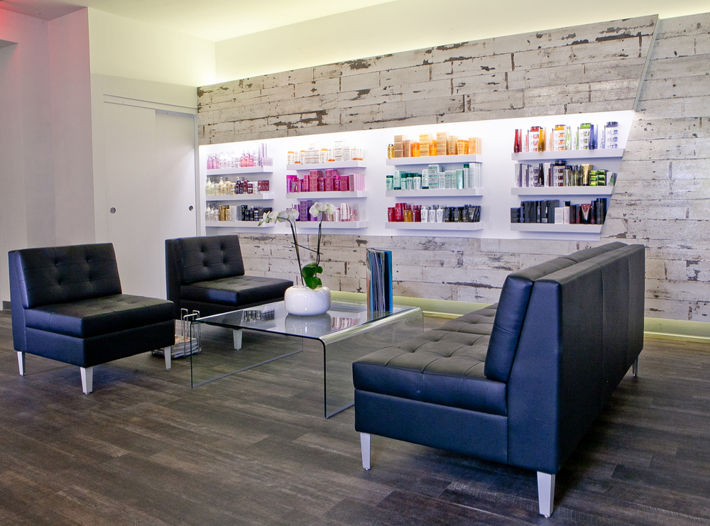 The waiting area boasts plush couches alongside the retail area that uses sleek floating shelves to display products fromL'Oréal Professionnel, Shu Uemura and Kerastase.