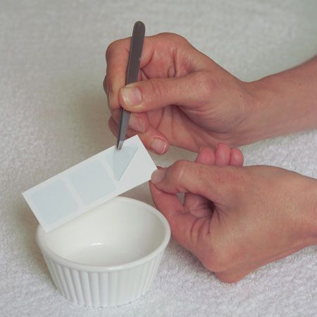 1. Prepare Filmo-Tech: Open one pouch and remove strip. Peel off only 1 piece (per treatment) of Filmo-Tech and place in a cup with 1 teaspoon of lukewarm water, mix well. Set aside. (Place remaining Filmo-Tech inside the pouch for preservation.