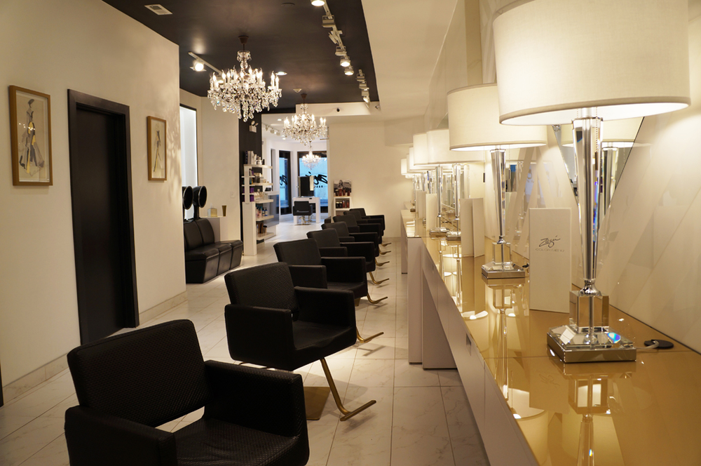 Custom black styling chairs with gold-coated bases are graced by crystal chandeliers.