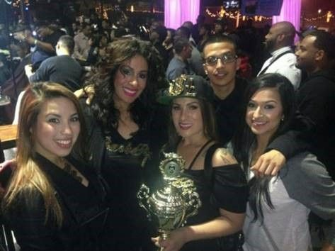 <p><strong><em>Angela Henning with trophy along with her sister and cousins – all licensed barbers.</em></strong></p>