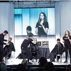 Ashley Holtz leads barbering demos on stage atthe World's Fair of Cosmetics Arts and Sciences...
