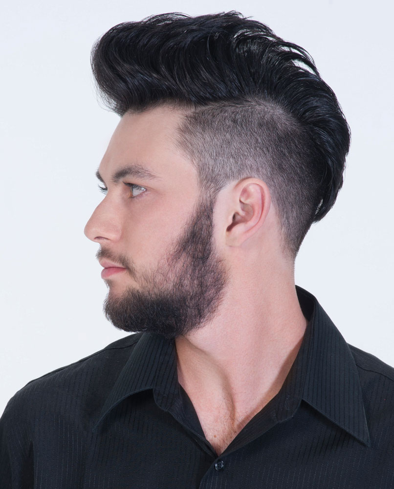 Robby is wearing a classic undercut with the top lengths styled into a pompadour.