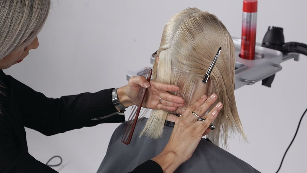 STEP 3: To start your layering, take a slightly diagonal forward parting and holding the hair at approximately 45°, create soft layering using a razor. Depending on the hair type, you can take deep vertical cuts, or softer texture holding your razor horizontally. As you move up, the elevation of each section is based off of the round of the head (approximately between 45° and 90°).
