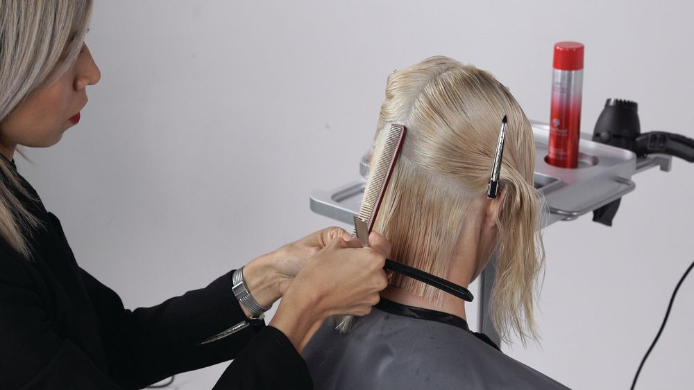 STEP 4A: To start your layering, take a slightly diagonal forward parting and holding the hair at approximately 45°, create soft layering using a razor. Depending on the hair type, you can take deep vertical cuts, or softer texture holding your razor horizontally. As you move up, the elevation of each section is based off of the round of the head (approximately between 45° and 90°).