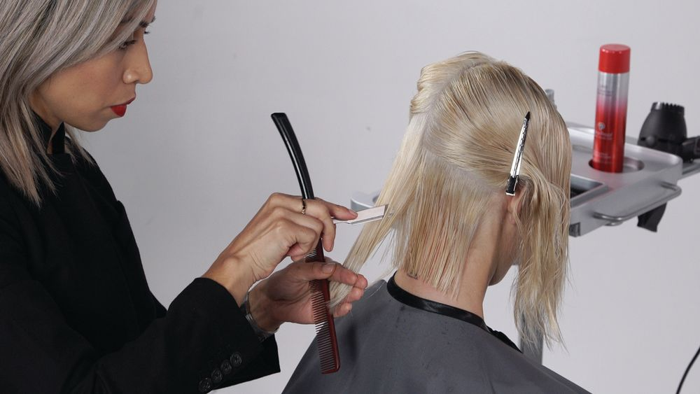 STEP 4B: To start your layering, take a slightly diagonal forward parting and holding the hair at approximately 45°, create soft layering using a razor. Depending on the hair type, you can take deep vertical cuts, or softer texture holding your razor horizontally. As you move up, the elevation of each section is based off of the round of the head (approximately between 45° and 90°).