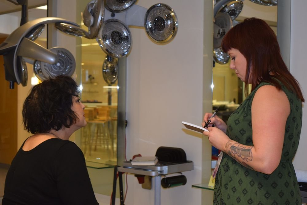 Attendee Carlee Smith consults with her client during a practical.
