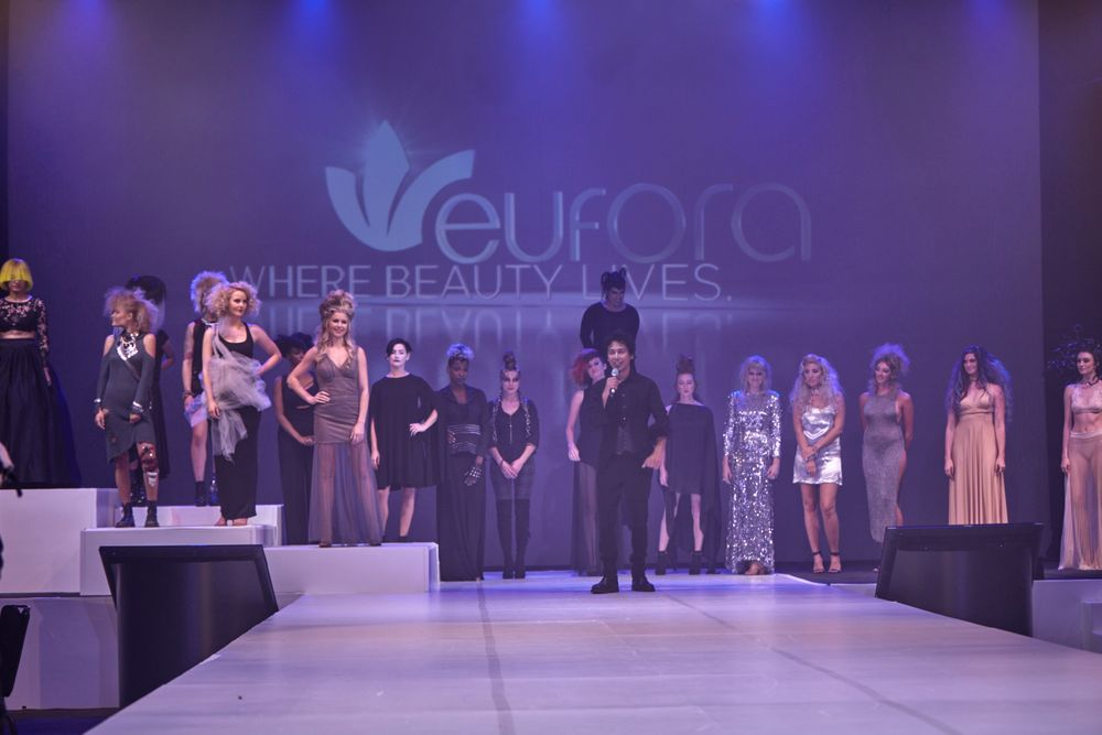 Philip Carreon surrounded by his models, onstage.