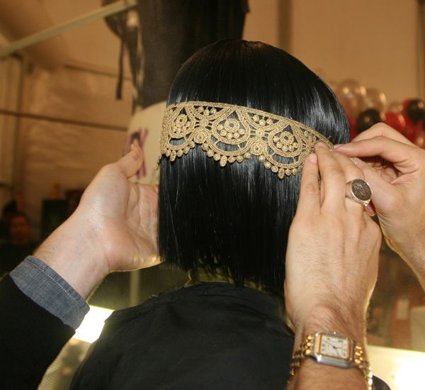 #8: Peter Gray pinning a piece of lace from ear to ear on the wigs, as a template.