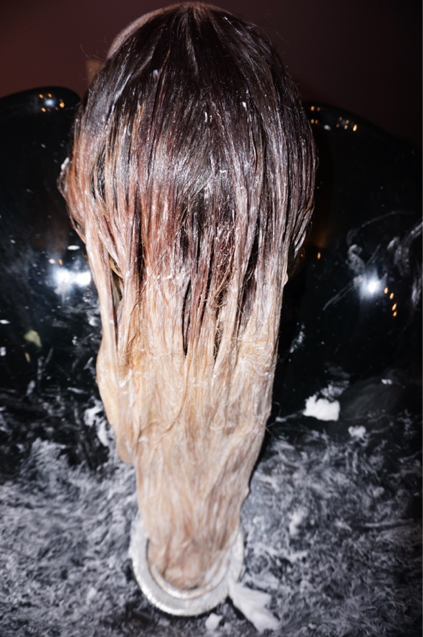 """Color-balance using: -Paul Mitchell Dual Purpose Lightener - 2 oz. -Paul Mitchell 30 volume developer - 2 oz. -Paul Mitchell Shampoo 2 - 2 oz.  Taking small sections, saturate the mid shaft to the ends, using balayage-like strokes. Bring the lightener closer to her base. Doing this will allow me to break up some of the previous color. """"It is extremely important to not leave your guest at the sink with the lightener on. Hair is unpredictable and can lift in an instant. The integrity of their hair is the most important!"""""""