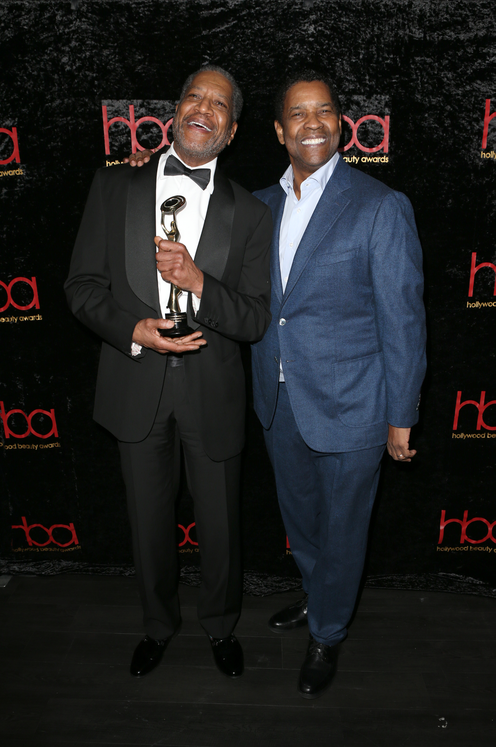<strong>Denzel Washington (right)</strong> presented <em>Outstanding Achievement in Hairstyling</em> to<strong> Larry M. Cherry</strong>, who has worked with the Oscar and Golden Globe winning actor for almost thirty years.
