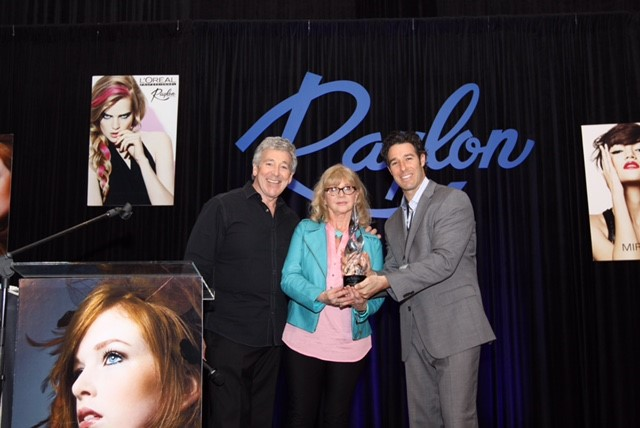Raylon CEO Howard Hafetz and Raylon President Josh Hafetz present the 2015 Art of Business Award to Intercoiffure America/Canada Vice President Sheila Zaricor-Wilson.