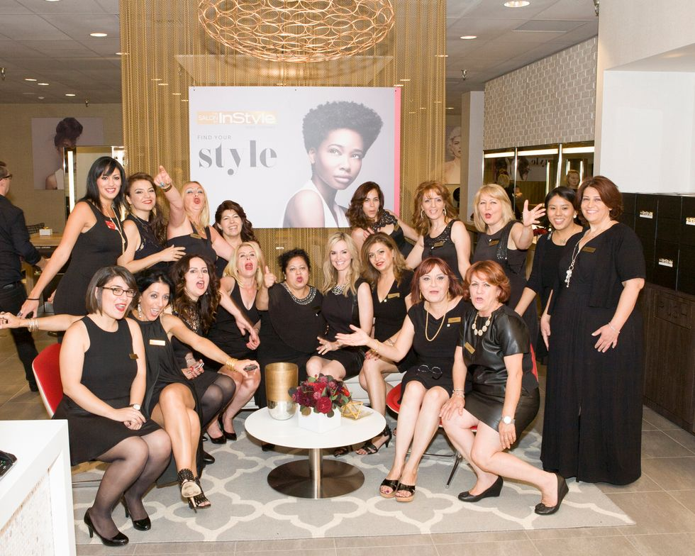 The celebrating salon team surrounds Amiee Thomas, vice president of salon at JCPenney.