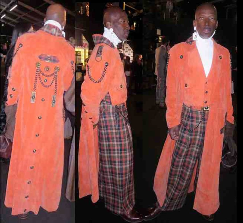 Fashion/jewelry designer, Phil Harris, in great long peachy orange corduroy coat with interesting details, worn with very wide tartan pants and one large earring, a hit in the Lobby during #NYFW.