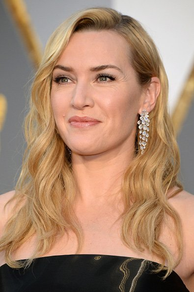 Kate Winslet let her hair down at the Oscars sporting honey haircolor, beachy, side-swept waves and a stunning black, Ralph Lauren floor-length gown. Kate Winslet let her hair down at the Oscars sporting honey haircolor, beachy, side-swept waves and a stunning black, Ralph Lauren floor-length gown. According to Hollywoodlife.com, Winslet's Oscar look was styled by stylist Renato Campora. To get the look, Campora prepped her hair with MarulaOil Rare Oil Style Extending Primer and then blow dried her hair with a round brush. To achieve the curls, Campora used the Paul Mitchell Neuro Unclipped 1-inch Styling Rod. The look was finished off with a strong hold hairspray.