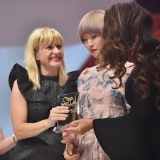 Manselle receives her trophy onstage for her 2015 North American Wella Trend Vision Award.
