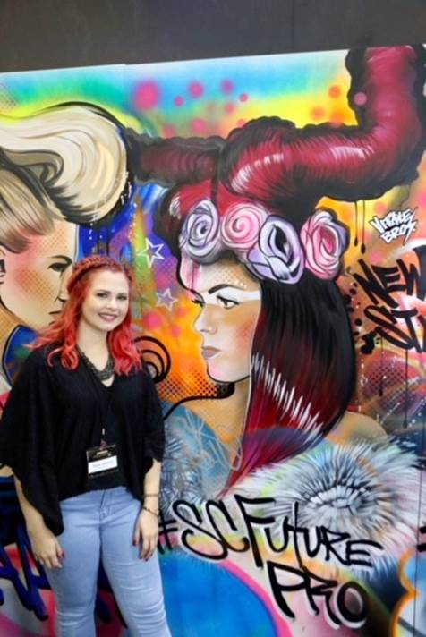 Kaylin Jackewicz, winner of the SalonCentric FuturePro Award, stands in front of the graffiti mural by St. Petersburg, Fla. muralists, The Vitale Bros.