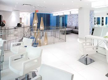 """The blue resin panels that we have throughout the salon, including up the stairway, give a hint of color throughout the pristine white space. Clients walking up the stairs always comment that it is like they are walking on water."""