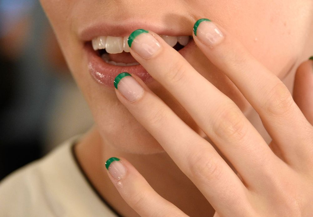 PUTTING IRRIDESCENT POLISH OVER A RED NAIL OR PAINTING A VIBRANT FREE EDGE ON A FRENCH CAN MAKE A BIG, BUT NOT OVERDONE, STATEMENT. Morgan Taylor lead artist Gina Edwards amped up a classic French at Monique Lhuillier by using a bold green polish at the tips.
