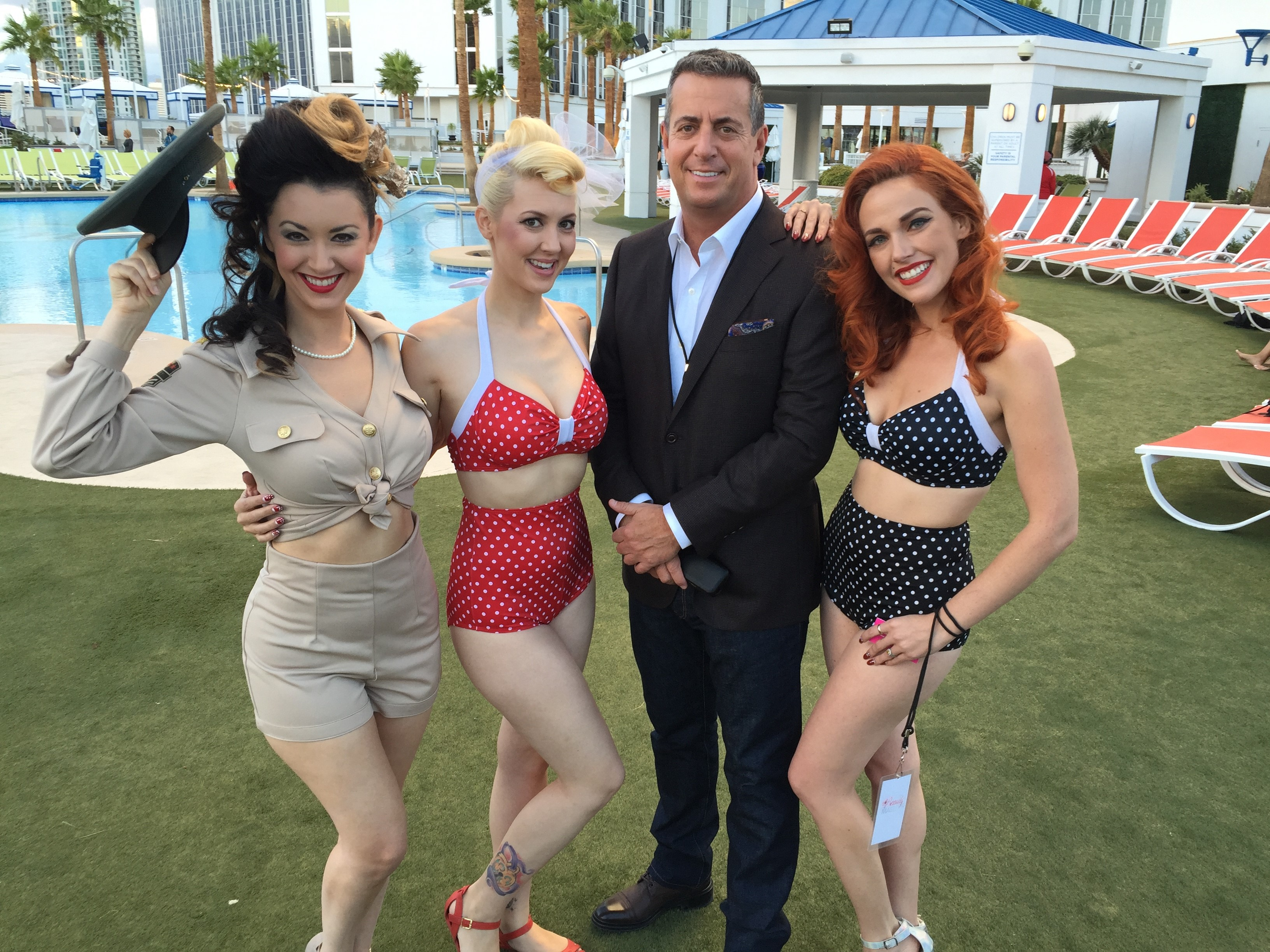 Kenneth Kahn surrounded by pin-up beauties at Global Beauty Masters.
