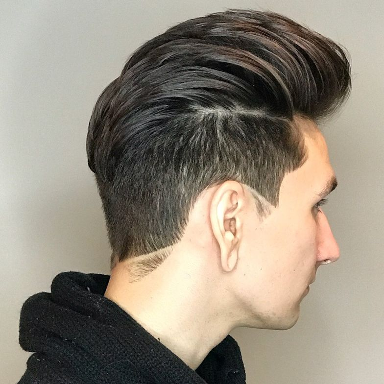 Sideburns are cut to match the nape for a cohesive, creative style.