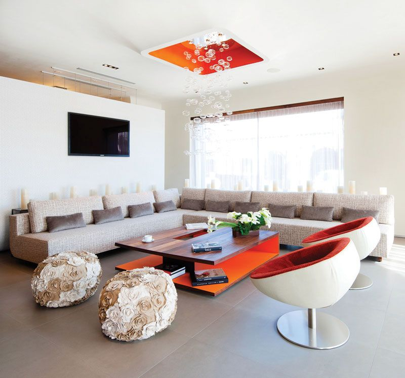 The in-house lounge combines the comfort of the living room with the vibe of a Hollywood hotspot—little bits of the unexpected, such as the pops of orange-red color, the bubble chandelier and the floral ottomans, add whimsy to the sleek, sophisticated furnishings.