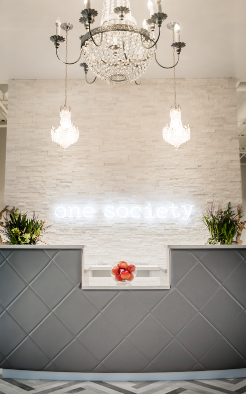The salon's logo in white pops against the stone wall behind the reception desk.
