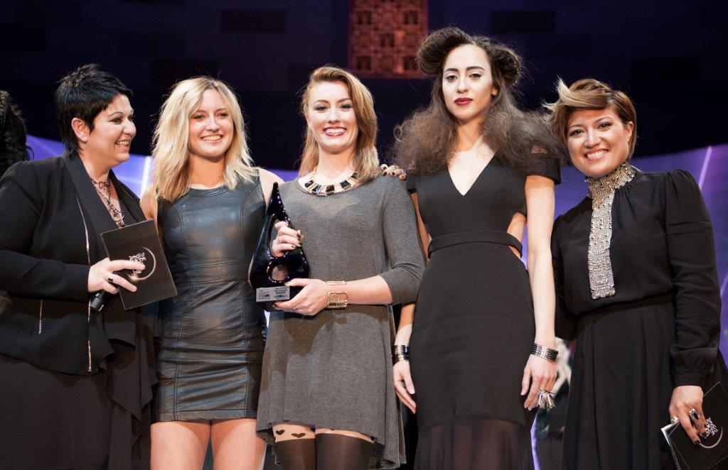 SAMANTHA PETERS, CENTER, SMILES WITH AWARD IN HAND AT THE WHAT'S NEXT AWARDS