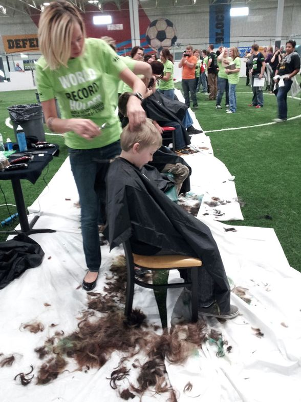 Roots Salon co-owner Naomi Prusinski preps a young participant in the Be Brave and Shave event.