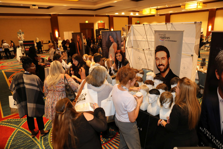Exhibitor tables on the show floor help attendees explore the products and services available to clients with thinning hair issues.