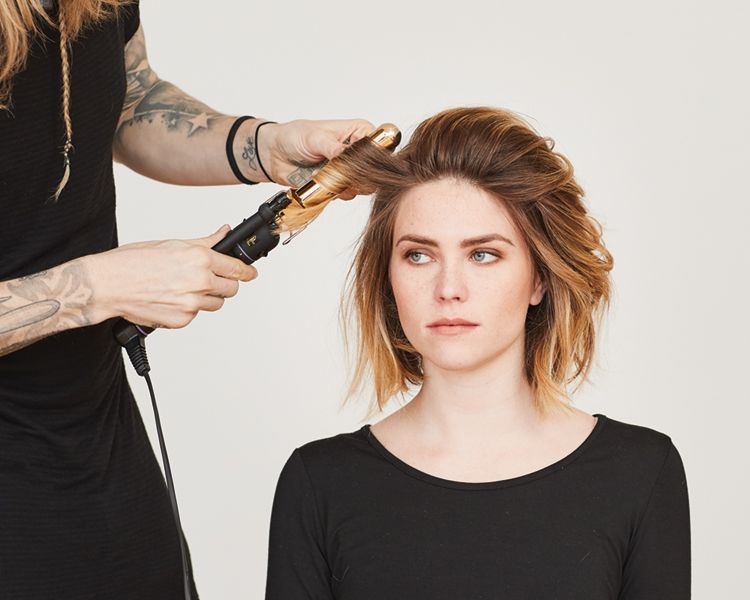 """<strong>Step 1: </strong>Using a 1 ¼"""" iron, start by curling the sides and bottom sections away from the face. Twist each section, leaving the last 2"""" out to create an undone look."""