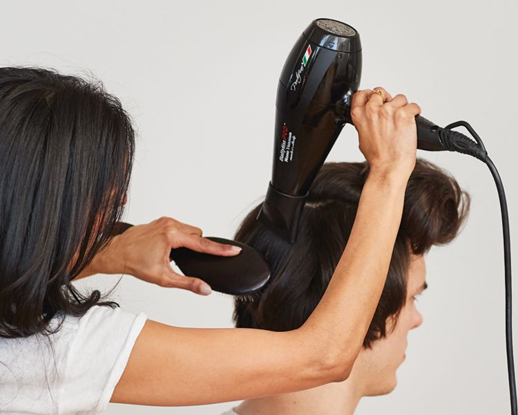 <strong>Step 2: </strong>Spray with <strong>Blowout</strong>, and use a flat brush to blow dry each section flat to the head.