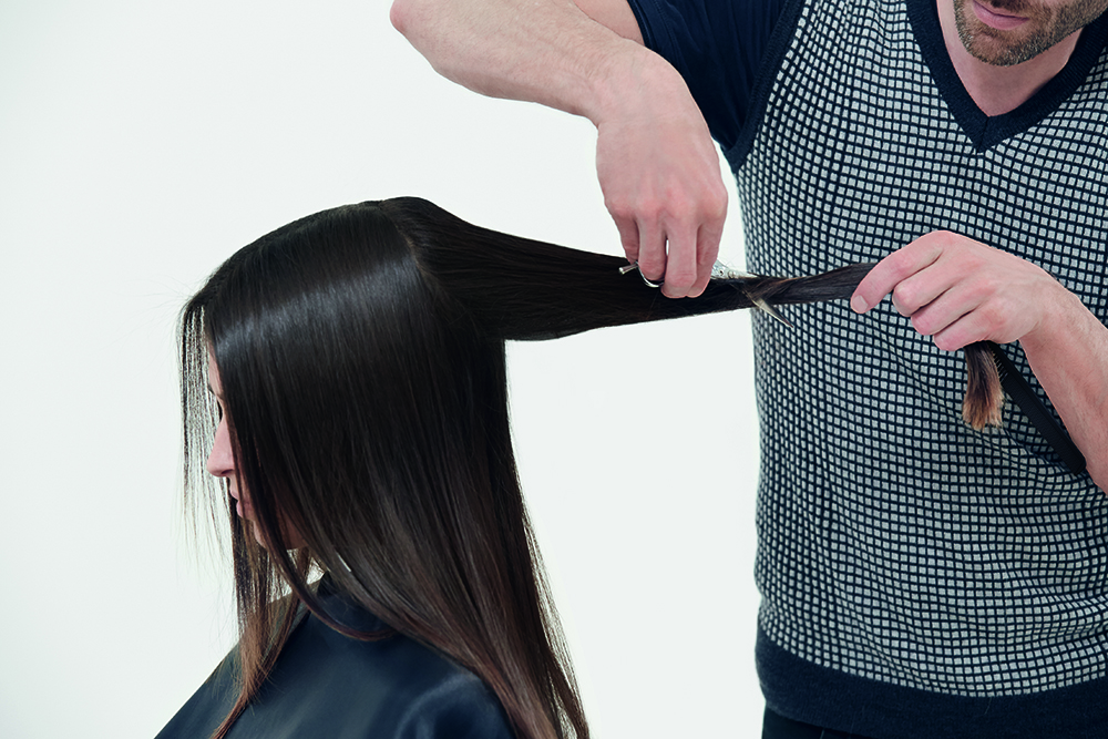 CUT STEP 1: Take a teardrop shape around the crown. Take the whole section and twist it. Then use your shears to slice the hair for very soft layering.